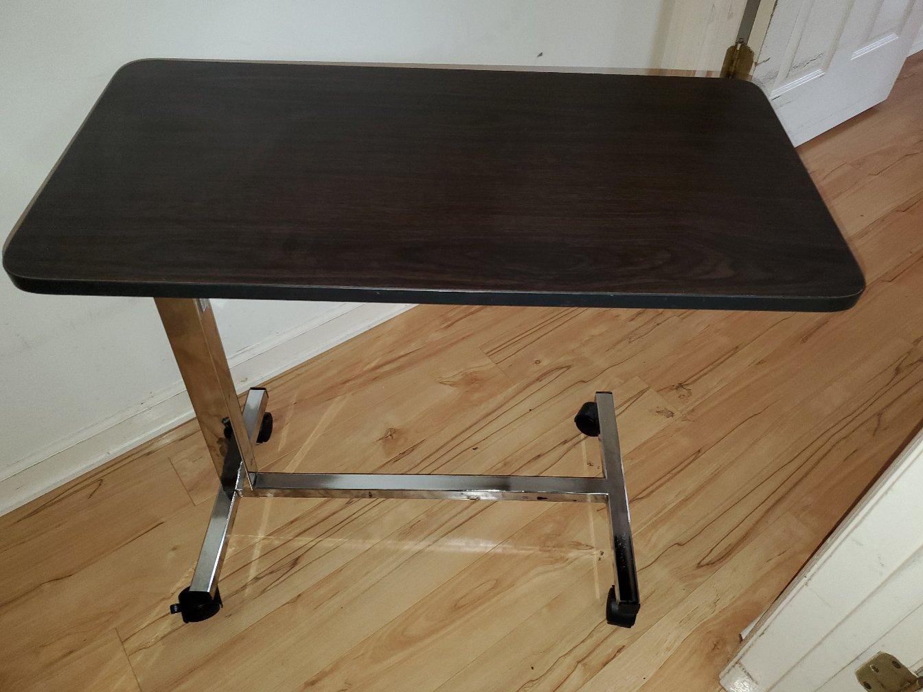 Photo 1 of adjustable hospital bedside table on wheels